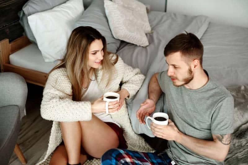 junges Paar im Schlafzimmer mit Kaffee sprechen