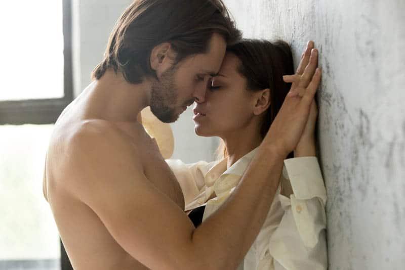 schöner Mann küsst Frau an der Wand