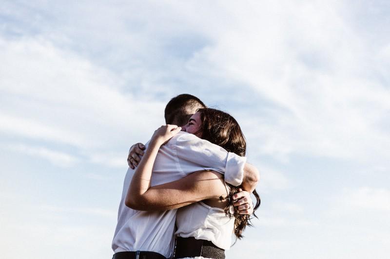 sehr glückliches Paar, das sich nach langer Zeit umarmt