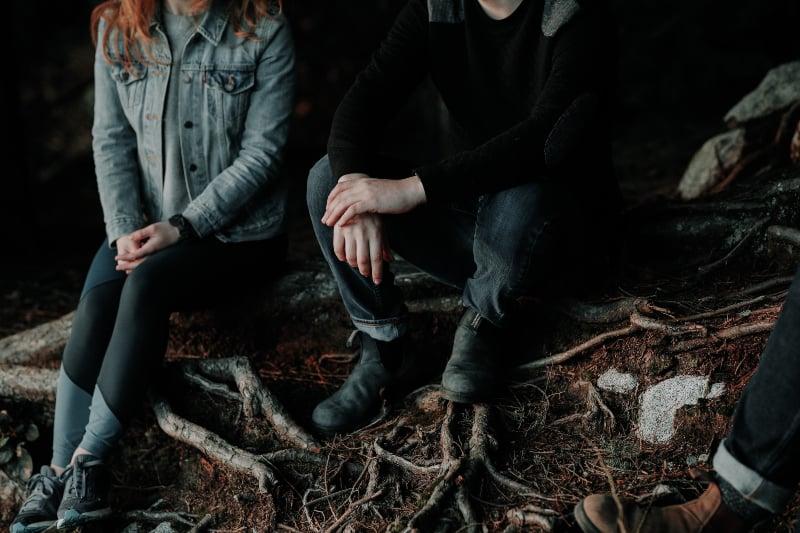 zwei Personen sitzen auf Holzplatte