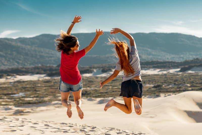 zwei glückliche Mädchen springen in der Wüste