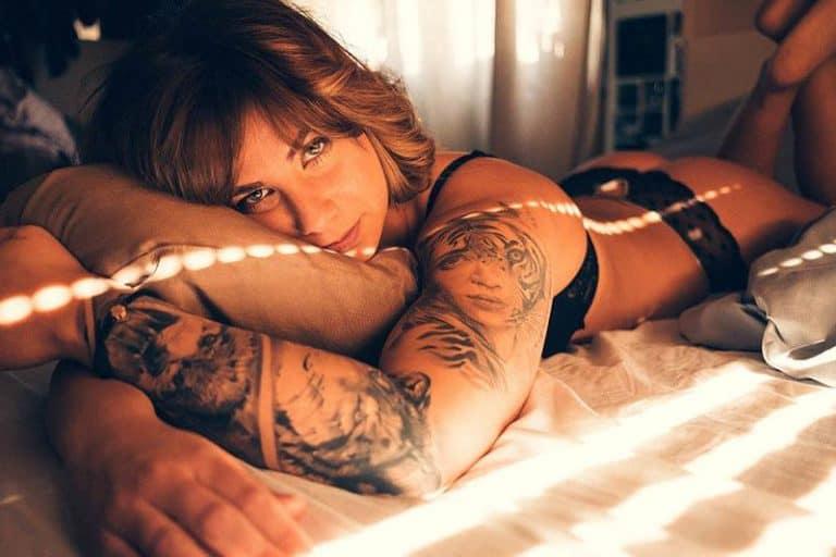 nackte tätowierte Frau auf dem Bett