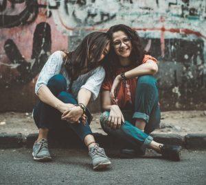 Zwei Frauen sitzen auf der Straße und lachen