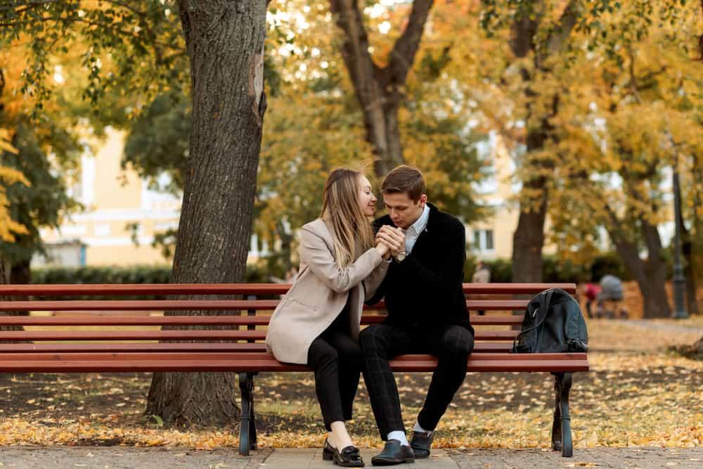 Auf einer Parkbank küsst ein Mann die Hände einer lächelnden Frau