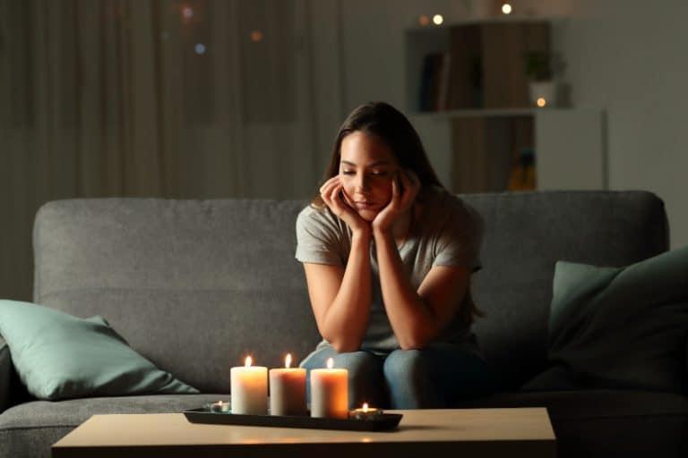 Das Mädchen sitzt auf der Couch und schaut auf die Kerzen