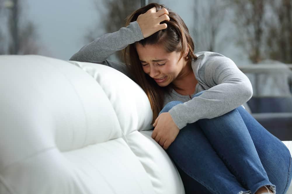 Die Frau auf der Couch sitzt und weint