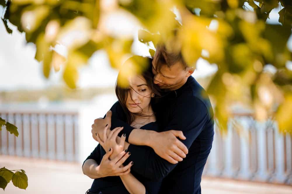 Draußen umarmt ein Mann eine Frau von hinten