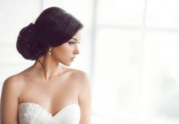 Ein Mädchen in einem weißen Hochzeitskleid steht am Fenster