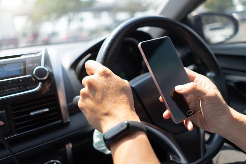 Ein Mann fährt Auto und benutzt ein Handy