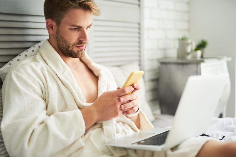 Ein Mann im Bademantel, der auf dem Bett sitzt und ein Handy benutzt