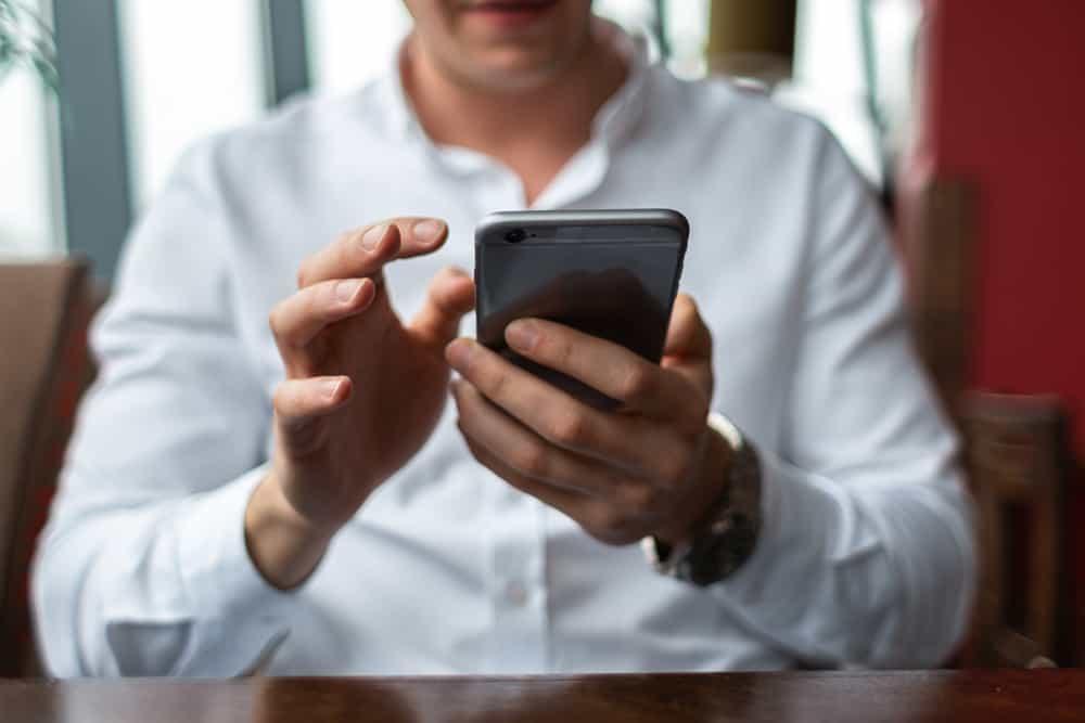 Ein Mann in einem weißen Hemd benutzt ein Smartphone