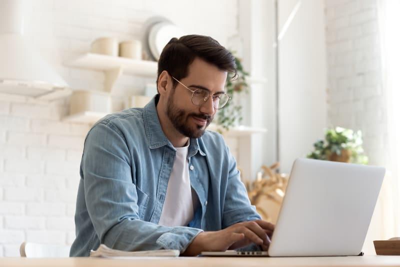 Ein Mann mit Bart benutzt einen Laptop