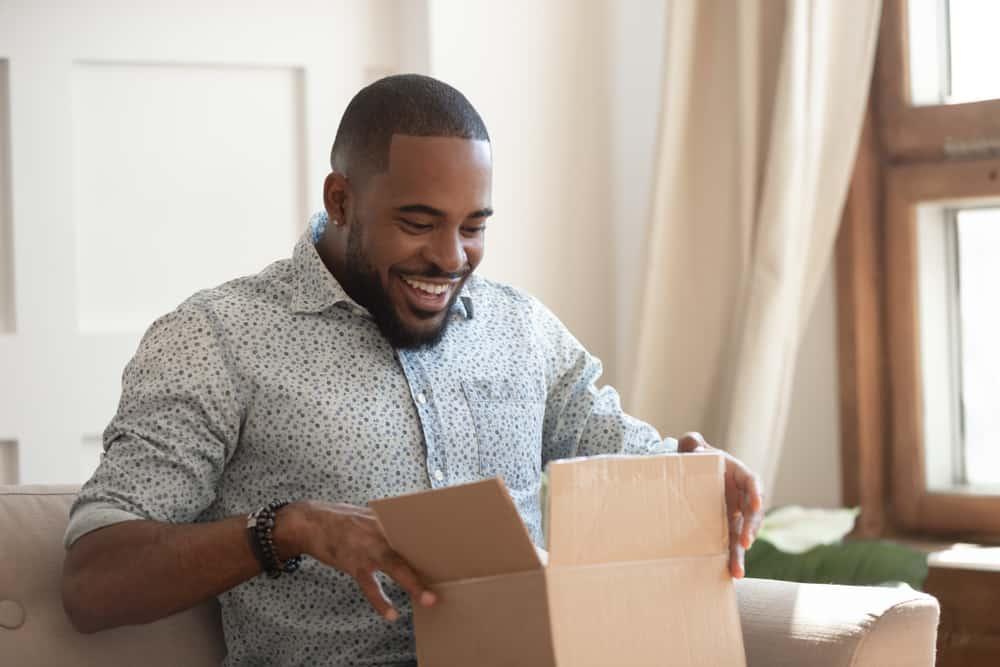 Ein lächelnder schwarzer Mann setzt sich und öffnet einen Karton