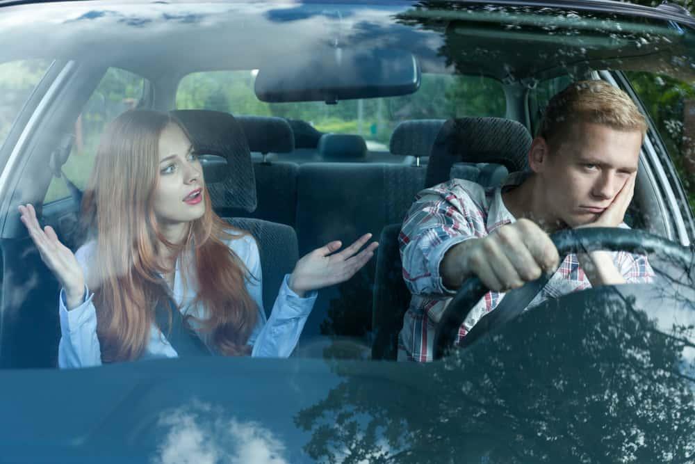 Ein wütender Mann im Auto hört seiner Frau zu