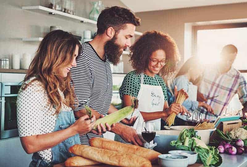 Eine Gruppe von Menschen in der Küche bereitet eine Mahlzeit zu