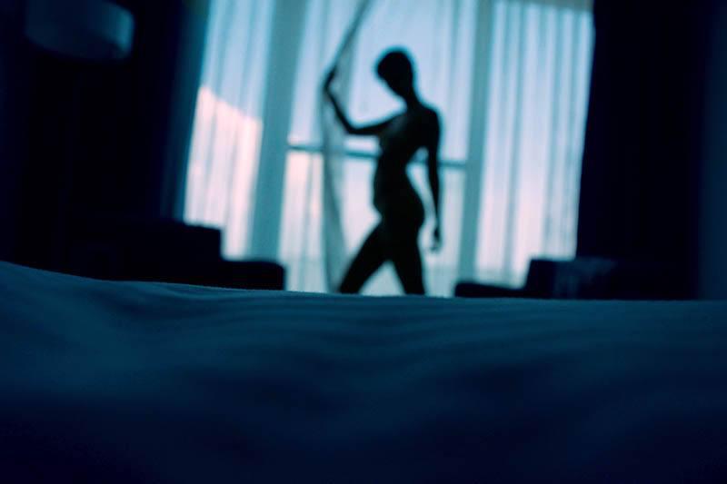 Eine hübsche Frau steht am Fenster in einem dunklen Schlafzimmer