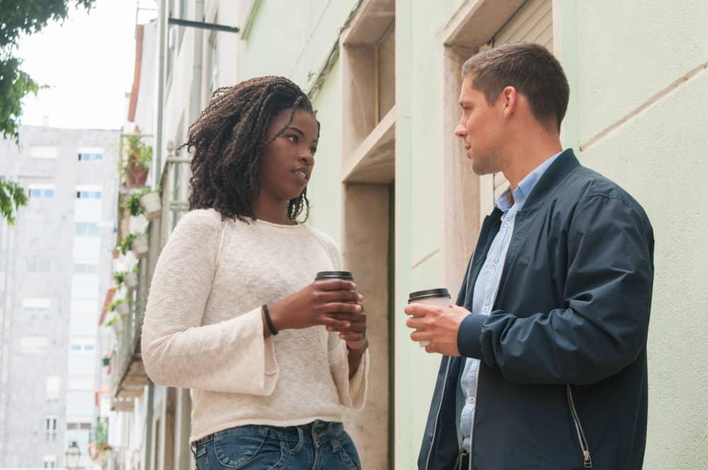 Eine schwarze Frau und ein weißer Mann auf der Straße führen ein ernstes Gespräch