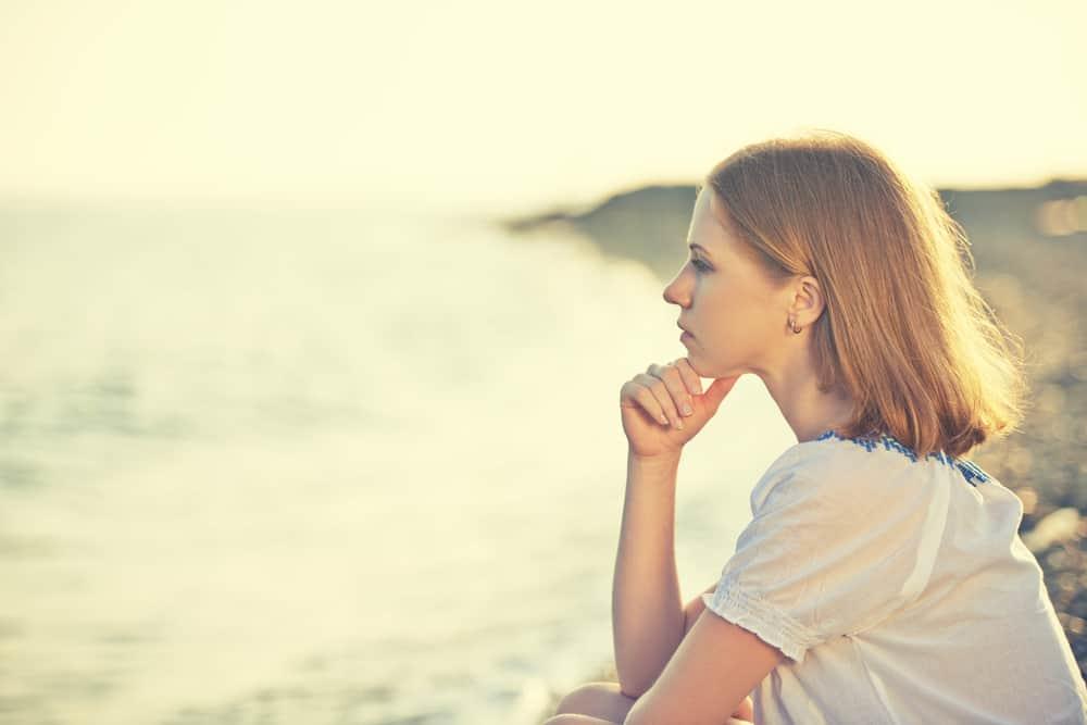 Eine traurige Frau schaut auf das Meer