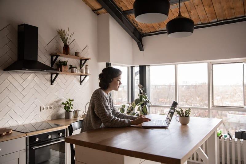 Frau in der Küche sitzt und knöpft auf Laptop