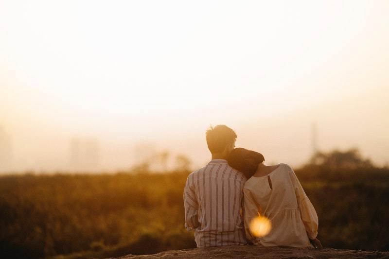 Frau legt Kopf auf Mannschulter, während sie Sonnenuntergang gegenübersteht