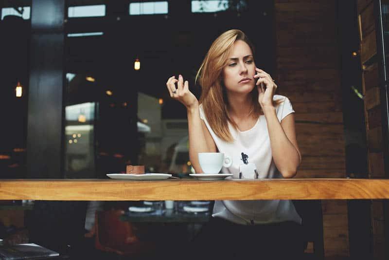 Frau sieht nachdenklich aus, während sie im Café telefoniert