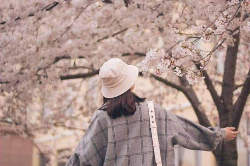 Frau trägt Hut und steht draußen