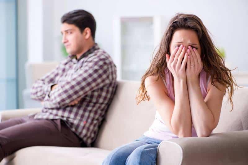 Frau weint, während ihr Mann hinten sitzt