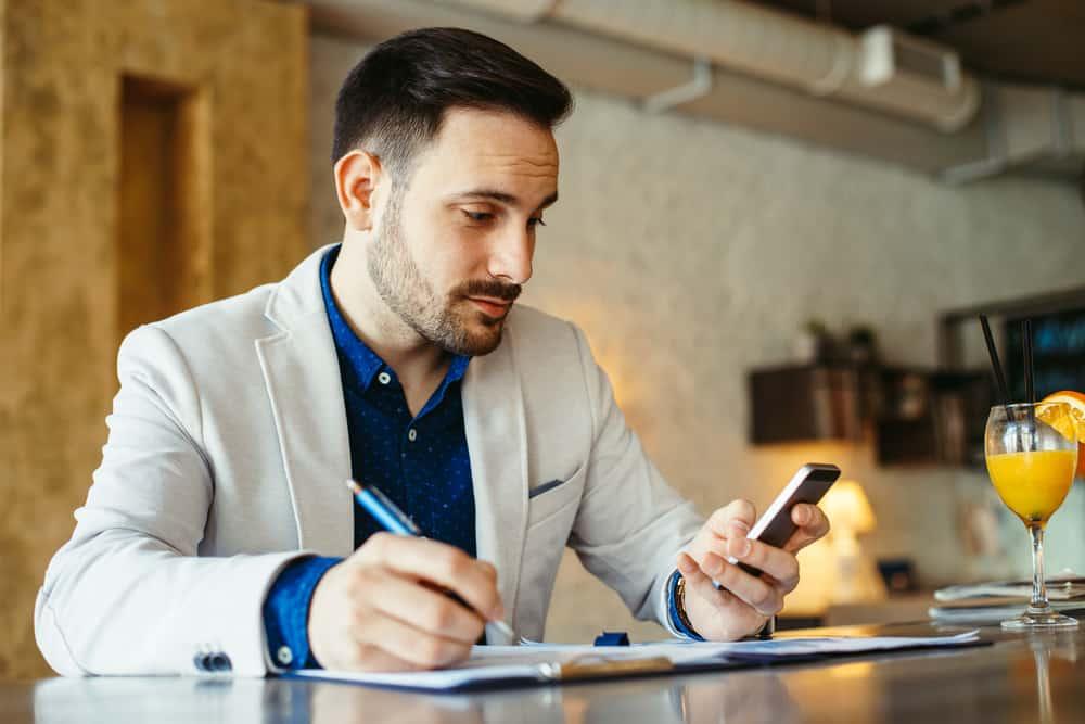 Geschäftsmann an seinem Schreibtisch schreibt SMS auf sein Handy