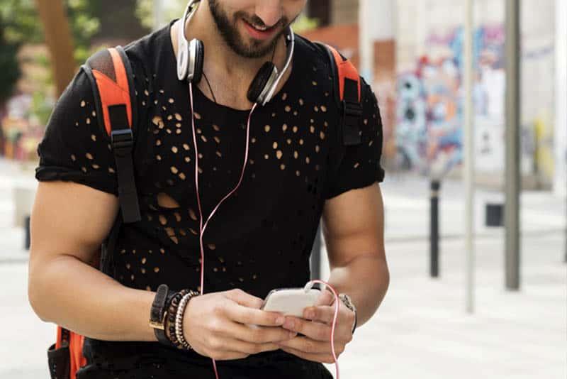 Mann im Kurzarmhemd, der draußen geht und Telefon benutzt