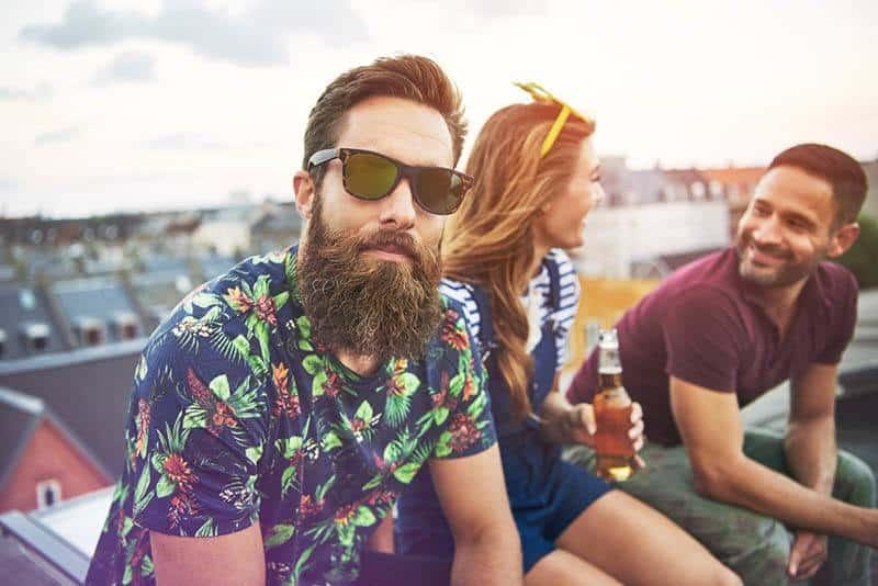 Mann mit Bart und Sonnenbrille schaut in die Kamera, während zwei Freunde hinter ihm sind