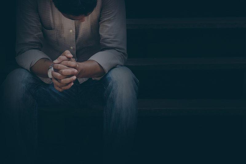 Mann sitzt und Händchen haltend