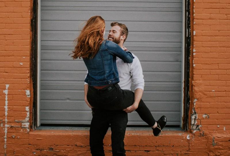 Mann trägt Frau in der Nähe von Rolltür