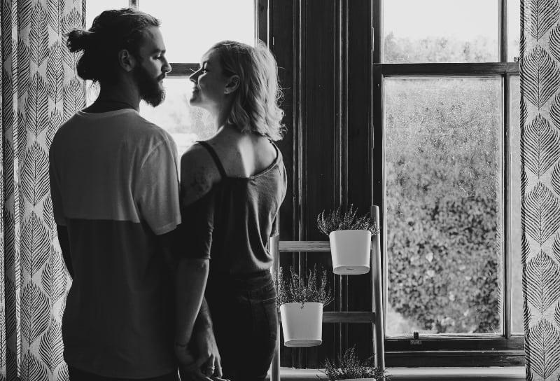 Mann und Frau stehen sich in der Nähe des Fensters gegenüber