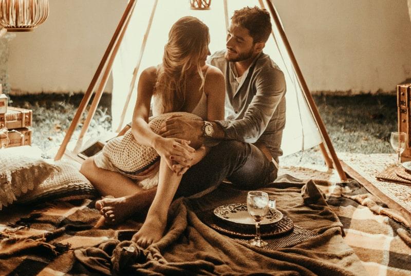 Paar sitzt in Tipi-Hütte mit Lichtern
