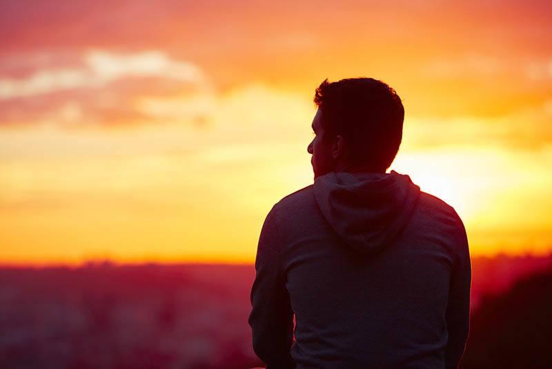 Rückansicht des Mannes, der draußen während des Sonnenuntergangs sitzt