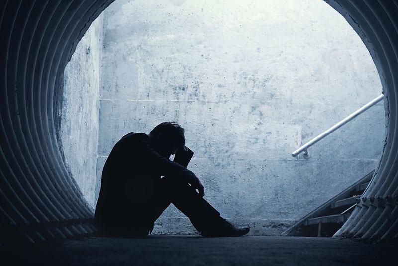 Seitenansicht des depressiven Mannes, der draußen sitzt