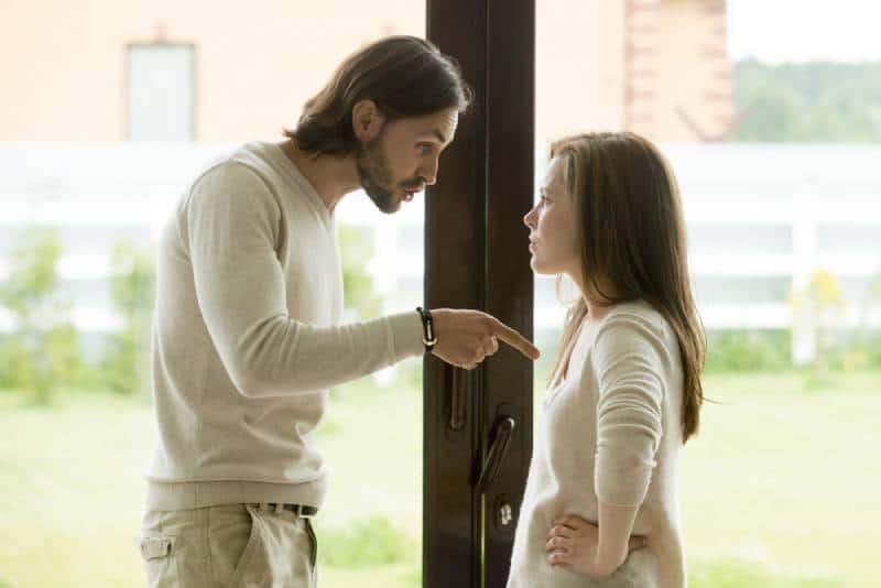 Unglückliches junges Paar, das an der Haustür stehend argumentiert