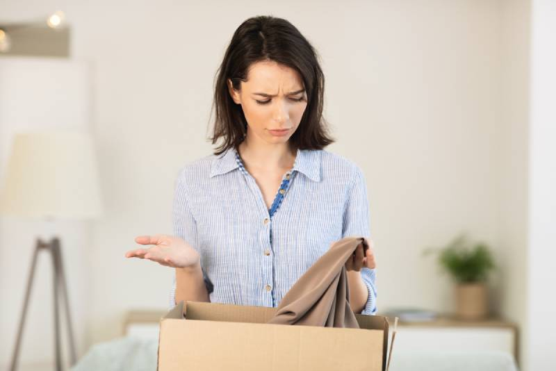 Verwirrte junge Frau, die Kleidung aus der Schachtel nimmt