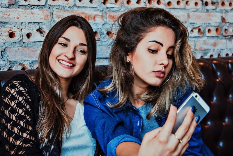 Zwei Frauen sitzen und fotografieren