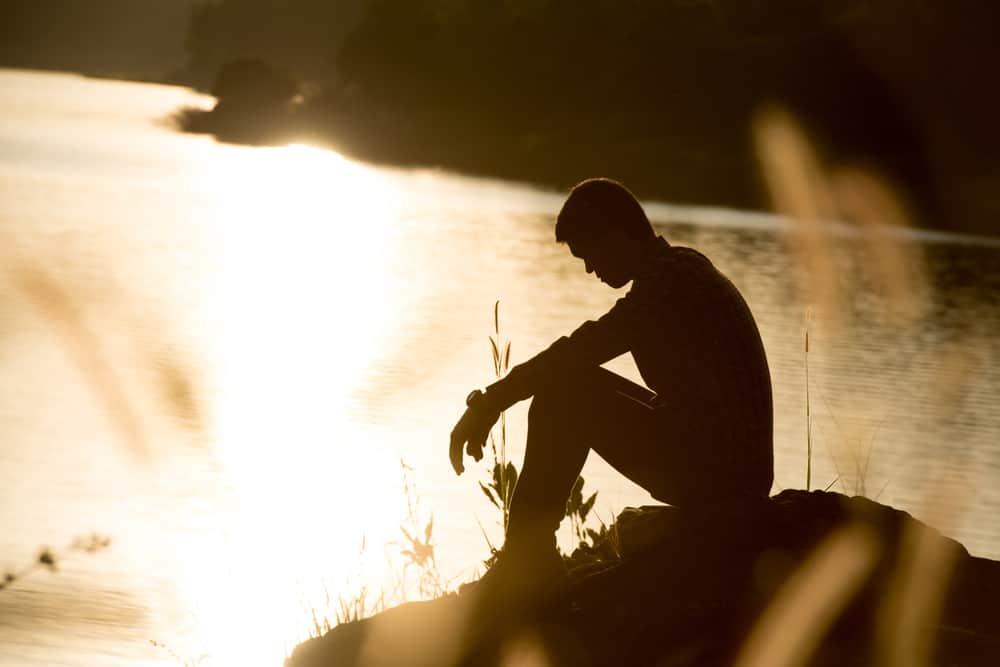 die Silhouette eines traurigen Mannes, der auf einem Felsen über dem Meer sitzt