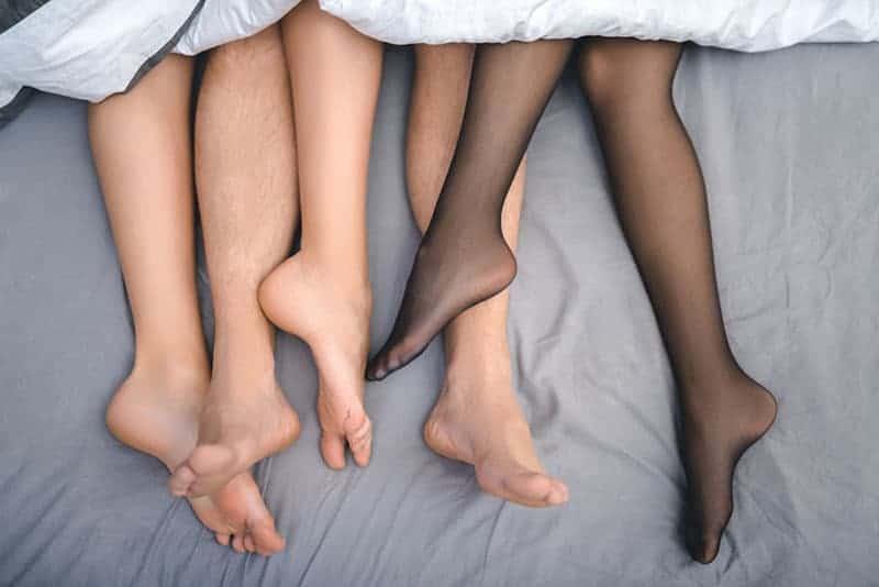 drei Beinpaare im Bett unter einem weißen Laken