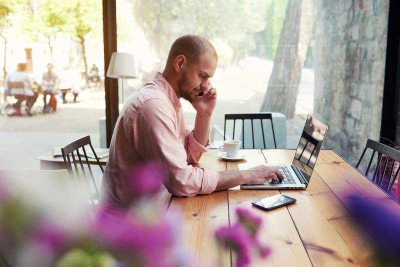ein Mann, der an einem Tisch sitzt und eine Nachricht auf einem Laptop schreibt