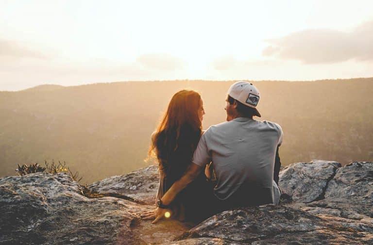 ein Paar, das die Spitze eines Berges genießt