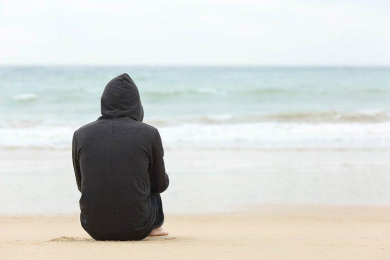 ein einsames Mädchen sitzt am Strand