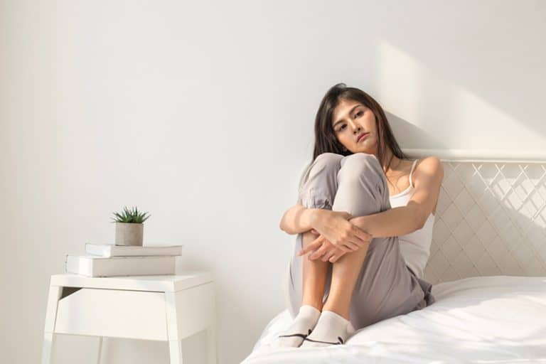 ein einsames Mädchen sitzt auf dem Bett