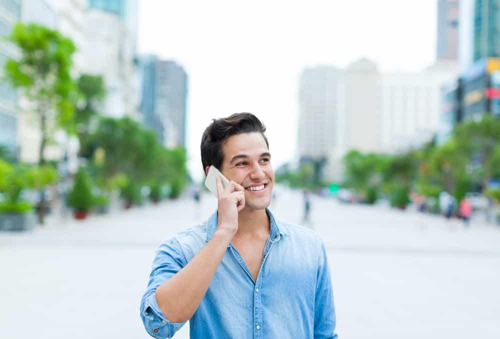 ein hübscher lächelnder Mann in einem blauen Hemd, der auf einem Handy auf der Straße spricht