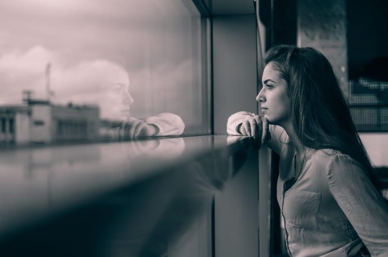 ein junges Mädchen, das das Spiegelbild ihres Charakters im Spiegel betrachtet