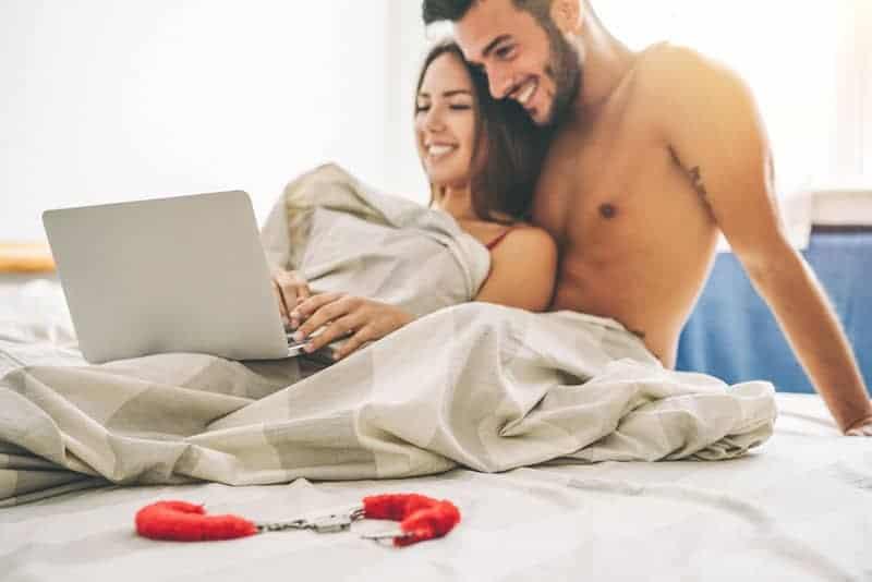 ein lächelndes Liebespaar im Bett, das etwas auf einem Laptop betrachtet
