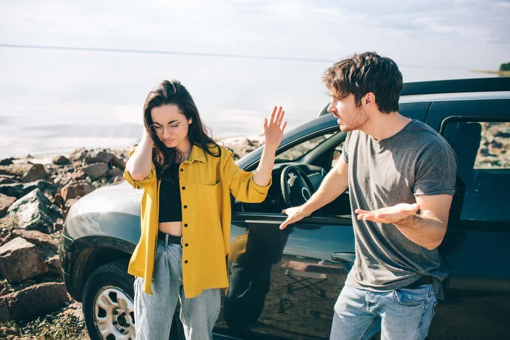 ein liebendes Paar, das neben dem Auto steht und streitet