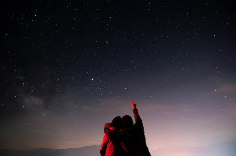 ein liebendes Paar in einer Umarmung, das die Sterne beobachtet